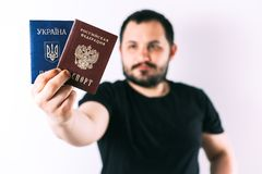 A man with a beard holding a passport of Russia and Ukraine translation: - Ukraine. Passport, Russian Federation. A man with a beard on a light background royalty free stock photography