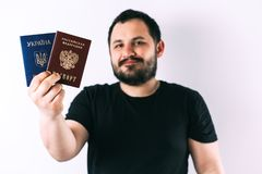 A man with a beard holding a passport of Russia and Ukraine translation: - Ukraine. Passport, Russian Federation. A man with a beard on a light background stock image