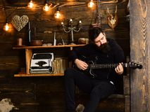 Man with beard holds black electric guitar. Guy in cozy warm atmosphere play music. Man bearded musician enjoy evening. With bass guitar, wooden background royalty free stock image