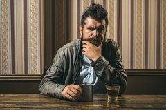 Man with beard holds glass brandy. Man holding a glass of whisky. Handsome stylish bearded man is drinking whiskey stock photography