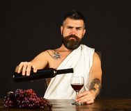 Man with beard holds glass of wine on brown background. Viticulture and crops concept. Sommelier pours expensive alcohol to taste. God Bacchus with strict face stock photos