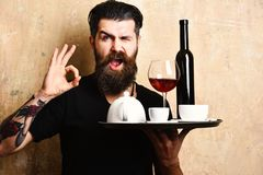 Man with beard holds various drinks on beige wall background. Barman with flirty face serves wine and tea showing ok sign. Cafe service concept. Waiter with Royalty Free Stock Image