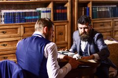 Man with beard interviews writer. Writer with busy fac. E use typewriter, works on new article with bookshelves on background. Journalism concept. Man in suit or stock photography