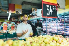 A man with a beard juggles with apples in the vegetable department of the supermarket. A man buys fruit in a store. Shopping in a supermarket Royalty Free Stock Photos