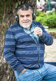 Man with beard listening to music. In a park Royalty Free Stock Photos