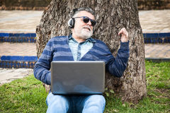 Man with beard listening to music. In a park Stock Image