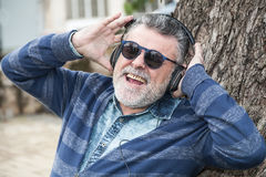 Man with beard listening to music. In a park Royalty Free Stock Image