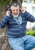 Man with beard listening to music. In a park Stock Photo