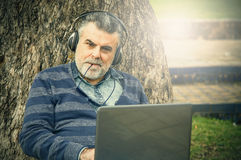 Man with beard listening to music. In a park Stock Photography
