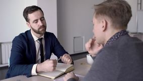 Man with beard listens to client in office at table to job in business. Serious businessman makes an interview with a male person and holds a pen over his stock video