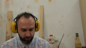 A man with a beard listens to music on headphones and sings stock footage