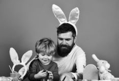Man with beard and little boy painting eggs for Easter. On green background. Easter celebration and joy concept. Father and son preparing for holiday. Dad with royalty free stock images