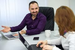Man with a beard at a meeting shows a girl laptop. royalty free stock image