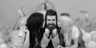 Man with beard and mustache attracts blonde and brunette girls. Girls fall in love with macho, kissing, pink background royalty free stock images