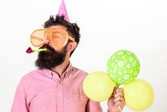 Man with beard and mustache on calm face holds air balloons, white background. Guy in party hat with party horn