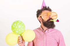 Man with beard and mustache on calm face holds air balloons, white background. Guy in party hat with party horn. Celebrates. Party concept. Hipster in giant stock images
