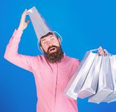 Man with beard and mustache carries shopping bags, blue background. Shopping concept. Guy shopping on sales season with. Discounts. Hipster on surprised face stock photos