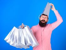 Man with beard and mustache carries shopping bags, blue background. Guy shopping on sales season with discounts. Shopping concept. Hipster on suffering face stock photos
