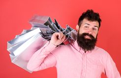 Man with beard and mustache carries shopping bags on shoulder, red background. Guy shopping on sales season with. Discounts. Shopping concept. Hipster on happy royalty free stock images