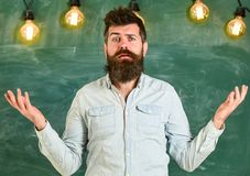Man with beard and mustache on confused face stand in front of chalkboard. Bearded hipster in shirt, chalkboard on. Background. Guy bewildered with confusing stock images