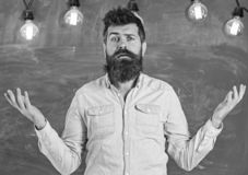 Man with beard and mustache on confused face stand in front of chalkboard. Bearded hipster in shirt, chalkboard on. Background. Guy bewildered with confusing stock photos