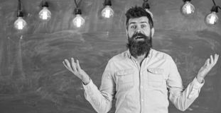 Man with beard and mustache on confused face stand in front of chalkboard. Difficulties concept. Bearded hipster in. Shirt, chalkboard on background. Guy stock images