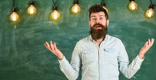 Man with beard and mustache on confused face stand in front of chalkboard. Difficulties concept. Bearded hipster in. Shirt, chalkboard on background. Guy royalty free stock images