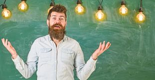 Man with beard and mustache on confused face stand in front of chalkboard. Difficulties concept. Bearded hipster in. Shirt, chalkboard on background. Guy royalty free stock photo