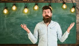 Man with beard and mustache on confused face stand in front of chalkboard. Difficulties concept. Guy bewildered with. Confusing expression. Bearded hipster in stock photos