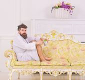 Man with beard and mustache enjoy morning while sitting on old fashioned luxury sofa. Luxury life concept. Man on. Thoughtful face in bathrobe drink coffee in stock image