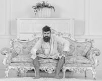Man with beard and mustache enjoys morning while sitting on luxury sofa. Man on sleepy strict face in bathrobe, drinks. Coffee, in luxury hotel in morning stock photography