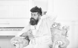 Man with beard and mustache enjoys morning while sitting on old fashioned luxury armchair. Man sleepy in bathrobe drinks. Coffee in luxury hotel in morning stock photography