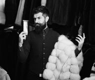 Macho with wallet in front furry clothes. Man with beard and mustache in fur shop. Macho with wallet in front of luxury furry clothes. Luxury clothing concept stock photos