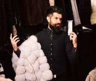 Macho with wallet in front furry clothes. Man with beard and mustache in fur shop. Macho with wallet in front of luxury furry clothes. Luxury clothing concept royalty free stock photos