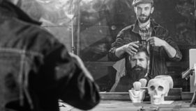 Man with beard and mustache in hairdressers chair in front of mirror background. Reflexion of barber styling hair of. Bearded client with comb. Hipster client stock photography