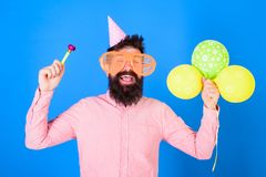 Man with beard and mustache on happy face holds air balloons, blue background. Party concept. Hipster in giant. Eyeglasses celebrating birthday. Guy in party Stock Images