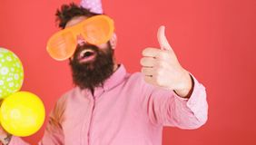 Man with beard and mustache on happy face holds bunch of air balloons, red background. Celebration concept. Guy in party. Hat shows thumb up gesture. Hipster in royalty free stock image