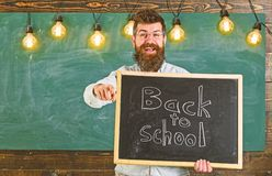 Man with beard and mustache on happy face invites students, pointing forward, chalkboard on background. Teacher in stock images