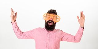 Man with beard and mustache on happy face wears funny big eyeglasses, white background. Cheerful mood concept. Hipster. Looking through of giant striped royalty free stock photography