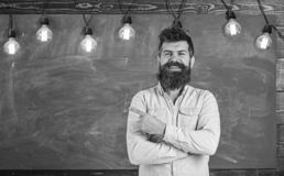 Man with beard and mustache on happy smiling face stand in front of chalkboard. Bearded hipster in shirt, chalkboard on stock photo