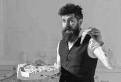 Man with beard and mustache holds box with tasty fresh hot pizza. Macho in classic clothes hungry, holds slice of cheese. Pizza, eats, enjoying taste, interior royalty free stock photo