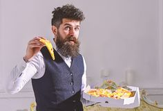 Man with beard and mustache holds box with tasty fresh hot pizza. Macho in classic clothes hungry, holds slice of cheese. Pizza, eats, enjoying taste, interior stock photo