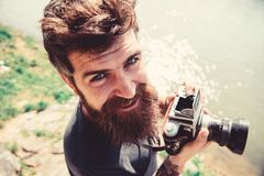 Man with beard and mustache holds camera, outdoor on sunny day, water surface on background. Photographer concept royalty free stock images