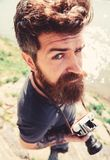 Man with beard and mustache holds camera, outdoor on sunny day, water surface on background. Photographer concept royalty free stock photo