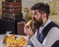 Man with beard and mustache holds delivered box with tasty fresh hot pizza. Pizza delivery concept. Macho in classic. Clothes hungry, on surprised face, bites Royalty Free Stock Photo