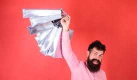 Man with beard and mustache holds shopping bags, red background. Guy shopping on sales season with discounts. Man. Caucasian hipster holding bunch of shopping royalty free stock image