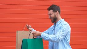 Man with beard and mustache holds shopping bags, red background. Guy shopping on sales season with discounts. Man. Caucasian hipster holding bunch of shopping stock video footage