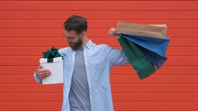 Man with beard and mustache holds shopping bags, red background. Guy shopping on sales season with discounts. Man stock footage