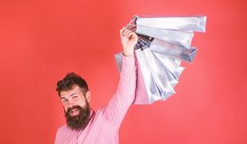 Man with beard and mustache holds shopping bags, red background. Guy shopping on sales season with discounts. Man. Caucasian hipster holding bunch of shopping stock photography