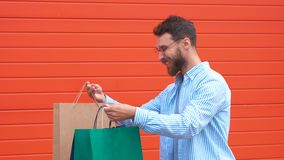 Man with beard and mustache holds shopping bags, red background. Guy shopping on sales season with discounts. Man. Caucasian hipster holding bunch of shopping stock footage